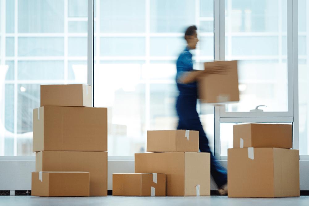 en man flyttar lådor till en magasinering