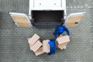 två anställda staplar lådor till en utrikesflytt